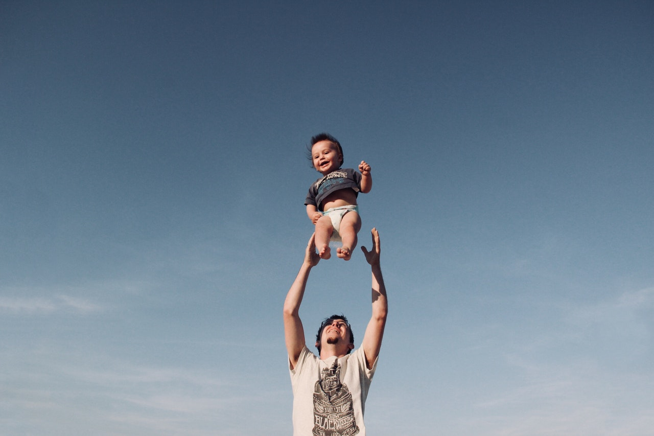 photo-of-man-in-raising-baby-under-blue-sky-1166990